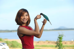 Image of  pretty woman pose and smile with green bird Royalty Free Stock Images