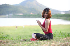 Image of Pretty woman sit on lawn play her smartphone and smile Royalty Free Stock Images