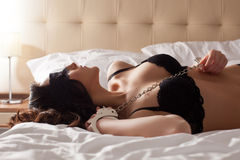 Image of pretty young submissive lying in bed Stock Image