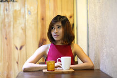 Image of pretty young woman sitting in the cafe with a cup of coffee Royalty Free Stock Image