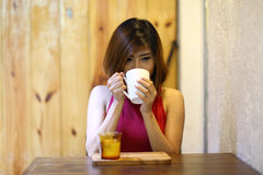 Image of  pretty young woman sitting in the cafe and drink coffee Royalty Free Stock Image