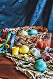 Image of the process of coloring Easter eggs at home. Easter. Eggs in a basket and colored paints on a wooden table. royalty free stock photography