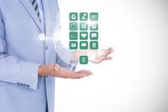 Image produite par Digital d'homme d'affaires tenant de diverses icônes sur le fond blanc Photos stock