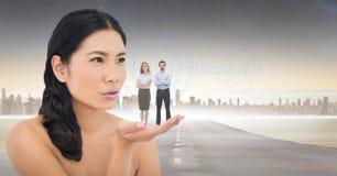 Image produite par Digital de femme avec des gens d'affaires se tenant sur la paume contre la ville Images stock