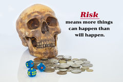 Image of psychology of investing concept. Human skull with dices and money coins and quote about investment risk Stock Photos