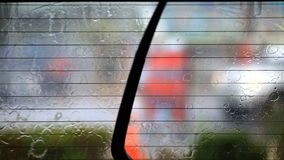 Image of rain drops falling on a car window with car wiper doing stock video footage