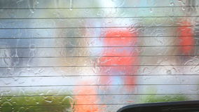 Image of rain drops falling on a car window with car wiper doing stock footage