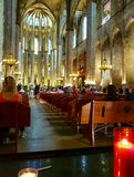 Image from rear of cathedral with burning candles while religiou Royalty Free Stock Photography