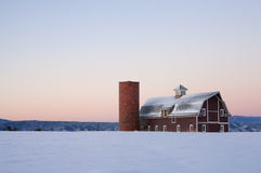 Image of a red barn with a field of snow stock images