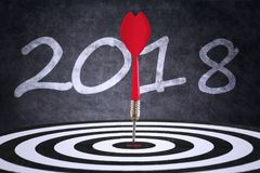 Red dart with numbers 2018. Image of a red dart on center of dartboard with numbers 2018 in the background Stock Image