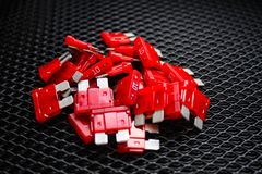 Image of red electric car fuses for 10 amps, on a dark background. Close-up royalty free stock photos