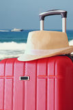 Image of red elegant travel luggage and fedora hat  in front of sea. travel and vacation concept Stock Images