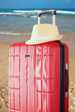 Image of red elegant travel luggage and fedora hat  in front of sea. travel and vacation concept Stock Photos