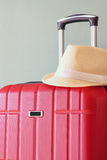 Image of red elegant travel luggage and fedora hat in front of sea. travel and vacation concept Royalty Free Stock Photography