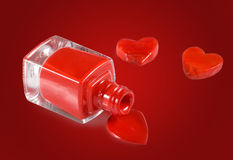 image of red nail polish and heart on red background Stock Images