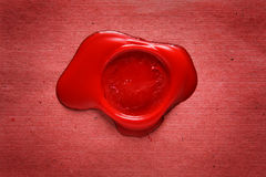 Image of red wax stamp over grunge background Royalty Free Stock Images