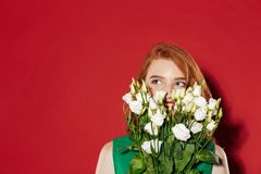 Redhead young girl covering face with flowers. Royalty Free Stock Images