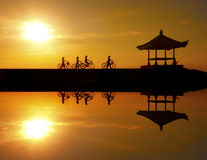 Image Reflection of cyclists riding on a concrete barrier in bali indonesia Sanur beach Royalty Free Stock Photo