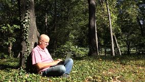 Image with Relaxed Person in Park Using Laptop Internet Connection.  stock photography
