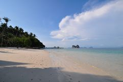 Image of a remote Thailand tropical island with deep blue skies, crystal clear waters, attap huts and coconut trees. Sandy beach on clear sky with small island stock image