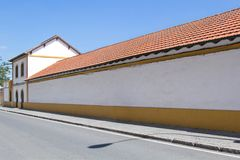 Blank, white wall by the street - clean space as a background for graphical mockup. Orange tile roof. royalty free stock images