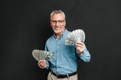 Image of rich good-looking adult man 60s with gray hair holding. Money two fans of 100 dollar bills and rejoicing his wealth isolated over black background Royalty Free Stock Photography