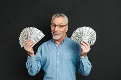 Image of rich happy adult man 60s with gray hair holding money t. Wo fans of 100 dollar bills and rejoicing his wealth isolated over black background Royalty Free Stock Photography