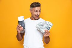 Image of rich man 30s in white t-shirt holding money fan and travel tickets. Isolated over yellow background royalty free stock photos