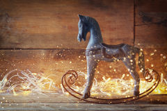 Image of rocking horse and magic christmas lights on wooden table Royalty Free Stock Image