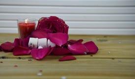 Image romantique de photographie de saison d'hiver avec les roses rouges et une bougie allumée avec le bonhomme de neige de somme Photographie stock