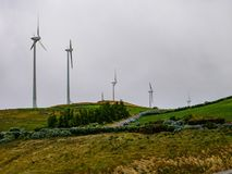 Image of a row of wind mills during unsettled weather stock photos