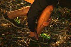 Image runner with pain in his leg. The man doing sports exercises and has a sore leg.Shot of sports shoes Stock Photo