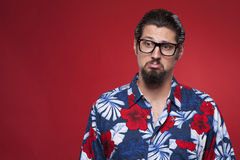 Image of a sad young man in Hawaiian shirt against red backgroun Royalty Free Stock Photography