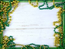 Image for Saint Patrick`s Day on March 17th. Shiny green and gold beads on a wooden frame with rustic woden background. royalty free stock photo