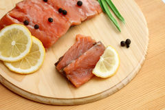 Image of salmon and lemon slices on cutting board. Top view of salmon and lemon slices on cutting board Royalty Free Stock Photos