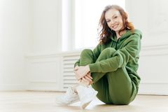 Image of satisfied refreshed young woman with foxy hair, keeps legs crossed, wears tracksuit and sportshoes, glad to have workout. Sits on floor in spacious royalty free stock images