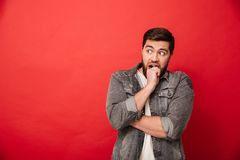 Image of scared man 30s in jeans jacket looking aside on copyspace and biting his fist in horror or fright, isolated over red. Image of scared man 30s in jeans royalty free stock images