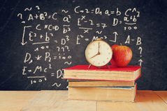 Image of school books on wooden desk, apple and vintage clock over black background with formulas. education concept Royalty Free Stock Photography