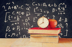 Image of school books on wooden desk, apple and vintage clock over black background with formulas. education concept Stock Photo