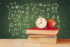 Image of school books on wooden desk, apple and vintage clock over green background with formulas. education concept royalty free stock photo