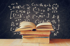 Image of school books on wooden desk over black background with formulas. education concept Royalty Free Stock Images