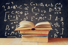 Image of school books on wooden desk over black background with formulas. education concept Stock Image