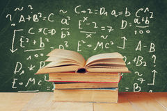 Image of school books on wooden desk over green background with formulas. education concept Royalty Free Stock Photos