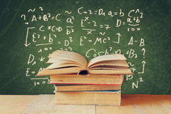 Image of school books on wooden desk over green background with formulas. education concept Stock Photos