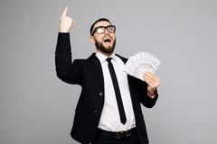 Image of screaming man in official suit standing isolated over grey wall background. Looking aside holding money have an idea poin. Image of screaming man in Stock Photos