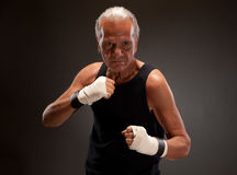 Image of a senior fighter posing against dark background Royalty Free Stock Photography