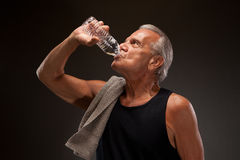 Image of a senior man drinking water. Senior man drinking water from a bottle Royalty Free Stock Photo