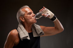 Image of a senior man drinking water after exercising. Senior man drinking water after exercising Royalty Free Stock Photo