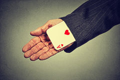 Image senior man hand pulling out a hidden ace from the sleeve. Closeup cropped image senior man hand pulling out a hidden ace from the sleeve isolated on gray Stock Photo
