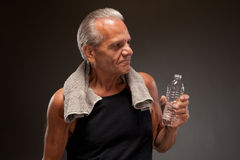 Image of a senior man posing with water bottle and towel Stock Image